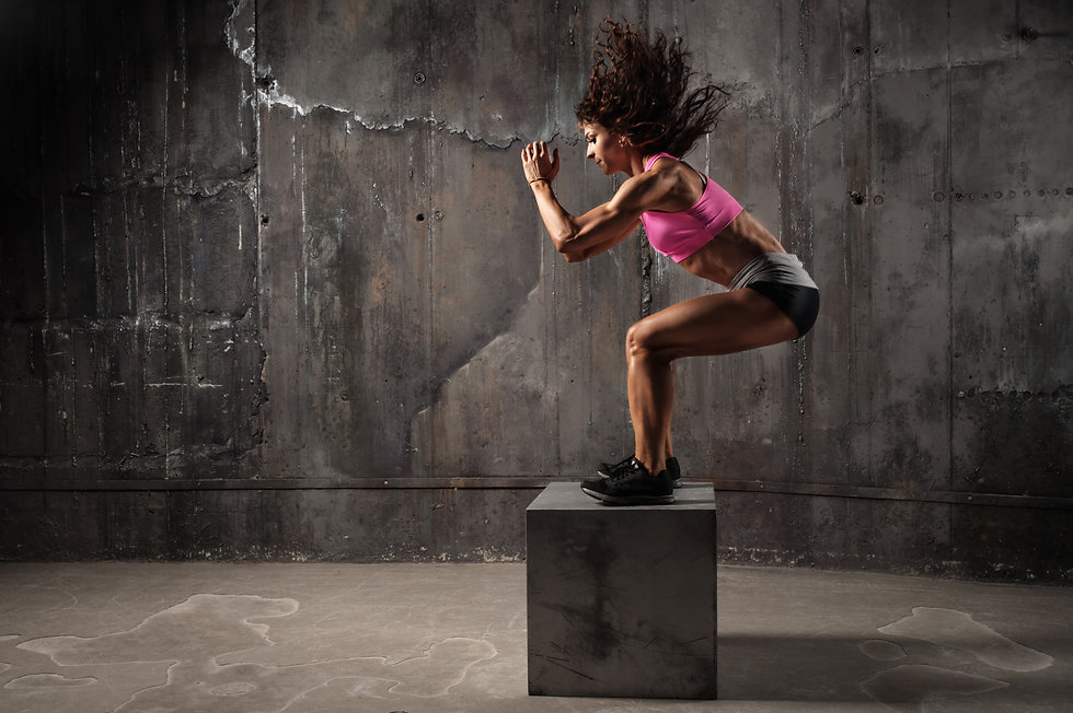 Fit young woman box jumping at a crossfi
