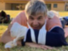 Adulto con discapacidad intelectual acostado en el pasto sonriendo