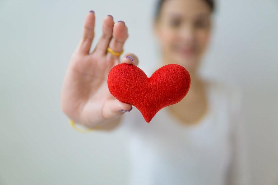 woman holding out heart shape.jpeg