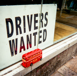 "Drivers Wanted by Richard Fletcher: March 2017 in MyLondon calendar and in 2016 exhibition. Richard Fletcher was walking past a taxi company on Old Street: ""First I just saw the bus and I thought 'oh, right, interesting' and then I saw the sign and I thought 'Oh my goodness.'"" Richard was doing landscaping in return for food and accommodation in East Grinstead. The job fell through and he came down to London last year. He sleeps rough in various places including King's Cross St Pancras and Victoria. ""During the summer it's alright. I had a night shelter during the winter months, which I may revert back to if I'm still here come October/November."" ""I met a fellow rough sleeper who knew about ART fitzrovia. I heard about the photography contest by chance. I was in a McDonald's late one night in Holborn and this guy walks in and he saw me sketching and he was the one who told me about Café Art."""
