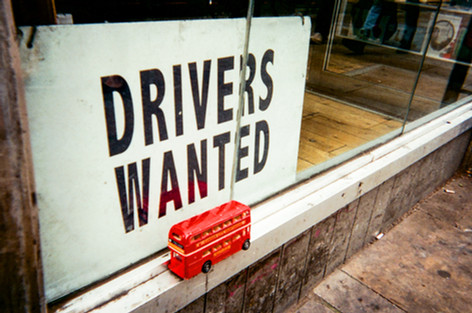 """Drivers Wanted by Richard Fletcher: March 2017 in MyLondon calendar and in 2016 exhibition. Richard Fletcher was walking past a taxi company on Old Street: """"First I just saw the bus and I thought 'oh, right, interesting' and then I saw the sign and I thought 'Oh my goodness.'"""" Richard was doing landscaping in return for food and accommodation in East Grinstead. The job fell through and he came down to London last year. He sleeps rough in various places including King's Cross St Pancras and Victoria. """"During the summer it's alright. I had a night shelter during the winter months, which I may revert back to if I'm still here come October/November."""" """"I met a fellow rough sleeper who knew about ART fitzrovia. I heard about the photography contest by chance. I was in a McDonald's late one night in Holborn and this guy walks in and he saw me sketching and he was the one who told me about Café Art."""""""