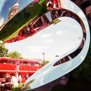 """London icons by Alana Del Valle: June 2017 in MyLondon calendar and in 2016 exhibition. """"I liked the way the sculpture framed the bus,"""" says Alana Del Valle. """"The artist who created it reminds us that metal is at times liquid or as soft as butter."""" Alana has been homeless off and on all her life, but is currently renting privately in what she describes as """"run-down housing"""" and suffers from depression as a result. """"This competition is invaluable in raising issues of homelessness and 'hidden' homelessness, it's one of the crises our city is currently facing, with little or no governmental solutions."""" A client at the Haringey Recovery Service run by St Mungo's, she says she is """"in the very early stages of recovery"""". She finds art helps as a way of expressing emotion. """"It's a useful tool for recovery. It can be quite therapeutic. We can use the camera to show our point of view, or homeless people's points of view of London or how they see the world, the negative or the beauty."""""""