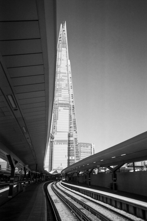 """NOVEMBER 2018: Trackside, Southwark: Hugh Gary took this shot of the Shard from London Bridge Station: """"I visited London Bridge to take a photo of the platform, turned around and seen the full length of the shard and thought the line of the platform canopy merges perfectly with the building."""" Hugh is an ex-serviceman, having been deployed to Iraq and Afghanistan during his ten years with the British Army. He became homeless two years later: """"a lot of the homeless people in London are ex-service"""". Hugh found shelter with West London mission's Big House, a hostel for veterans and is currently waiting for his own place through Stoll, who seek to rehouse veterans across London. He has now in his final year of a Photography degree, at the University of West London. Where he founded a photographic society, to support his fellow students. He has also started offering his photography skills to mentor young adults, some of which are homeless through the Pillion Trust and, Café Art and their partners."""