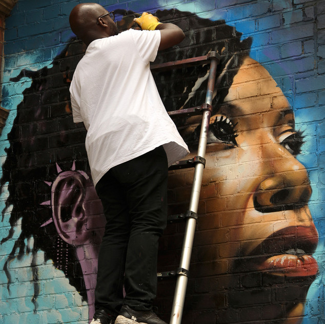 World renowned London based British Ghanaian artist Neequaye Dreph was finishing off his mural when he was captured by photographer Krzysztof Wlodarczyk. This particular piece is the 7th subject of Dreph's 'You Are Enough' series of portraits painted across London paying tribute to inspirational black women who are doing amazing things for their communities and society at large. In 2013 photographer Krzyszof Wlodarczyk had a winning photo in the first MyLondon photography contest. He is now a member of the Café Art photography mentoring group run by volunteers from The Royal Photographic Society which meets up every two weeks to learn photography skills with digital cameras. Copyright: 2017 Qbic Hotels & Cafe Art