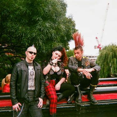 "MARCH 2018: Punk Rockers, Camden Town: Jackie said it was a hot day so a good day to visit Camden Lock Market. ""They"" were happy to pose for the camera. While not as common as they used to be, you can still see punks around Camden Town most weekends"" says Jackie, ""especially when it's hot"". Jackie goes to the Haringey Recovery Service, which is run in partnership with St Mungo's, where she does voluntary meditation teaching. ""It's important to share what people have given to you and never forget where you come from,"" Jackie says. ""Never ever look down on anybody unless you're picking them up."" ""I love London. It' a cosmopolitan city with a lot of culture. I like taking pictures, especially in my favourite haunts, Alexandra Palace and Hampstead Heath."""