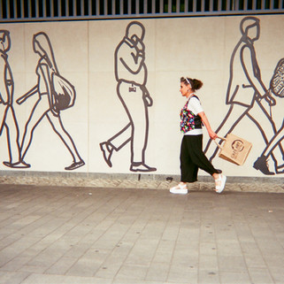 "SEPTEMBER 2018: Commuters, City of London: Michelle Goldberg directed her friend to take this shot of herself walking in front of Julian Opie's CitizenM mural at Tower Hill Station. Last year Michelle got a photo in the exhibition and she's very happy to get into the calendar this year. ""I'm a Londoner. I was born here. My family have been here four generations, possibly five. My grandparents were in the markets."" Michelle has a long term medical condition and lives in temporary accommodation. ""I've had four heart attacks, three strokes, a lung collapse."" ""My background is in the Arts. I did my bachelors' at Kingston School of Art and then I worked for a year in the West End and then I went to the Royal College of Art in Kensington – Fashion Department… I grew up in the industry. There were factories all over London which are now very expensive flats and everything is made outside of the country so we have lost a really important creative industry. London's a really wonderful, colourful, inspiring, creative place for people. This project is kind of bringing back some of that spirit of London, albeit in an ironic situation."""