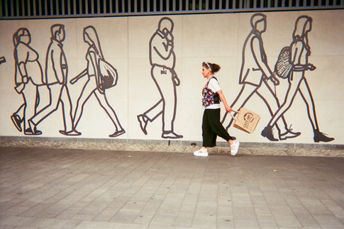 """SEPTEMBER 2018: Commuters, City of London: Michelle Goldberg directed her friend to take this shot of herself walking in front of Julian Opie's CitizenM mural at Tower Hill Station. Last year Michelle got a photo in the exhibition and she's very happy to get into the calendar this year. """"I'm a Londoner. I was born here. My family have been here four generations, possibly five. My grandparents were in the markets."""" Michelle has a long term medical condition and lives in temporary accommodation. """"I've had four heart attacks, three strokes, a lung collapse."""" """"My background is in the Arts. I did my bachelors' at Kingston School of Art and then I worked for a year in the West End and then I went to the Royal College of Art in Kensington – Fashion Department… I grew up in the industry. There were factories all over London which are now very expensive flats and everything is made outside of the country so we have lost a really important creative industry. London's a really wonderful, colourful, inspiring, creative place for people. This project is kind of bringing back some of that spirit of London, albeit in an ironic situation."""""""