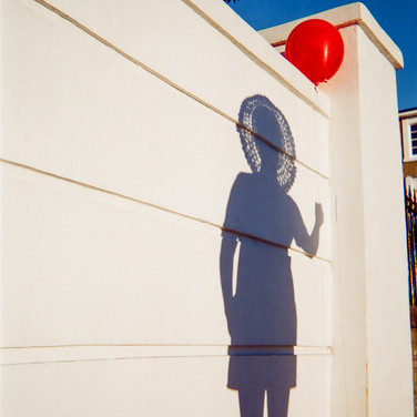 "JULY 2018: Shadow Play, Islington: ""This photo was taken in Hemingford Road Islington whilst I was out for a walk with my daughter on a sunny Sunday afternoon. I happened to have a red balloon in my bag so I blew it up whilst I found an amazing shadow of my girl on the wall with it. I loved the optical illusion that it created of her holding the balloon."" Born in London , Ella grew up on the south west coast of Ireland . She returned to London over 20 years ago and now lives in Islington. She is a trained hairdresser. She has just finished a pre-foundation course in Art and Design at Mary Ward Centre in London where she hopes to continue with her studies in September. She goes to art sessions run by SHP near Essex Road, Islington. ""I was having some problems with my housing so that was why I got referred to SHP. I've had good support from them."""