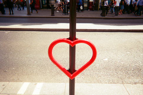 """Love heart bike stand by Ella Sullivan: February 2017 in MyLondon calendar and in 2016 exhibition. """"I was in New Bond Street when I happened to notice this love heart bike stand and thought it would make a great picture as it was giving out a message of love and providing a safe place to lock up your bike ."""" Born in London, Ella Sullivan grew up in County Kerry, Ireland. She returned to London over 20 years ago and now lives in Islington. Ella says she sometimes takes photos on her phone, but doesn't have a real camera. She goes to art sessions run by SHP near Essex Road, Islington. """"I've been going to SHP art group for over a year now. I was having some problems with my housing so that was why I got referred to SHP. I've had good support from them."""" She is also doing a course with the London Hairdressing Apprenticeship Academy in Camden. """"I finished doing the hairdressing course last year so now I'm working on the barbering side of it doing men's haircuts."""""""