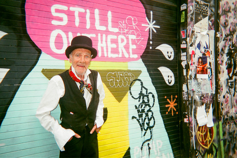 """JANUARY 2018: Still Here, Brick Lane: """"This is Mick Taylor, known as 'Teapot', 'Little Harvey' and more nick names"""" says photographer Lou Danby. """"Lots of people know him as he's been round a bit. People had thought he was dead so I took a photo of him in front of this mural on Brick Lane!"""" Mick grew up in Clapton, Hackney but has lived near Spitalfields for years. Lou says he's one of the last proper Cockneys. His upbringing was hard and they were very poor, says Lou. """"At the same time, he had a lot of fun and there was a lot of love."""" Mick, 72, met Lou five years ago. """"She's a great help. She comes around and takes me for walks."""" Lou enjoys going down to the Nomadic Gardens, """"a really nice piece of waste land next to the railway tracks near Brick Lane where everyone sits around doing artwork and being really nice. It's a place where people can go and broaden their horizons."""""""
