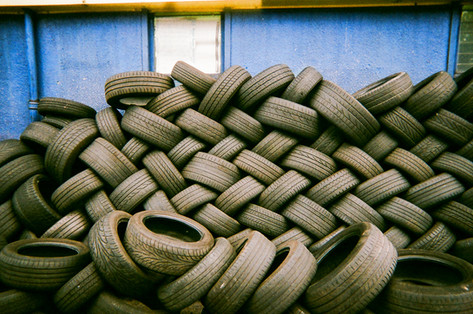 """Tyre pile by Mia Lyons: In 2016 MyLondon exhibition. Mia Lyons took this photo in a car repair garage just off Truro Road, Palmers Green, London. """"Maybe it's a bit too deep but I thought about our consumerism and how much we throw away and use and that we have to become more kind as a society and kinder to the earth that we live from. But now we know and we can change our behaviour, it's nothing negative it's just making people more aware."""" Mia is originally from Hamburg, Germany and has lived in London for six years. She says the last time she took photos was when she was 14. She teaches pottery at Haringey Recovery Centre, which she describes as a supportive environment. """"I see it as my oasis. I was a client I started a dual diagnosis and I went there for counselling. My best friend was homeless and now she lives in a hostel. We have so much in common we stick together and we help each other out."""""""