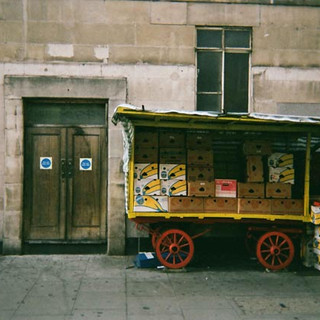 November in 2014 Cafe Art calendar. This photo was taken on Warren Street by Paul Duffy who said he went there purposefuly to get a shot of the cart which he had seen 'with and without fruit' for years. He said he got up early and was there at seven in the morning, adding 'I didn't want anyone to be in it.' Paul is from Glasgow and used to care for his mother and father before they passed away about five years ago. He currentlu lives with about 40 other people who are homeless in a hostel run by Shelter from the Storm in Islington. He was referred to then by the Thames Reach day centre in Camden Town where he goes during the day. His next step will hopefully be helped by an organisation called Second Step who will find him a permanent place to live.