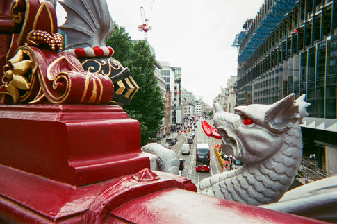 EXHIBITION ONLY: Dragon bridge, Holborn: On my daily walk over the Holborn viaduct I noticed the dragons tongue and the black knight helmet had a perfect triangular frame. I then waited for a London bus to pass to make it complete the shot.