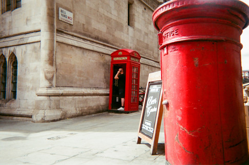 """MAY 2018: London Icons, Westminster: Tim Paul took this shot in Bell Lane, near the Strand. He says the post boxes and telephone boxes are symbolic to London. """"There's something about red: red boxes, red buses. I kept thinking about London being red… I saw a guy called Jon with a bike standing behind the phone box and I asked him if he wouldn't mind standing in it for this shot"""". Tim is an artist at 240 Project in West London. """"They have helped me with my self esteem. When I came I was in a bad place mentally – very depressed, low self esteem. People here don't ask too many questions so I can be myself. Everyone just accepts each other here."""" Talking about the MyLondon contest, Tim says he had never used film before and found the project a challenge because of the limited number of shots. The 240 Project recently had an exhibition of photos and he said one of the """"biggest buzzes ever"""" was to sell one of his photos."""