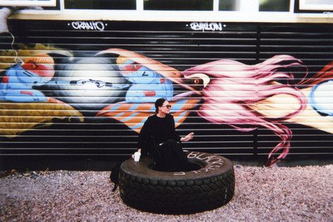 Photo by Desmond, chosen by public vote for January in 2016 My London calendar. Desmond Henry took this image of a woman talking a coffee break in front of a mural by Brazilian street artists Cranio, Bailon and Sliks, near the Pritchard's Road Day Centre, Hackney. 'I was very lucky, it was as if God sent her.' Desmond was born in Northamptonshire and grew up in the West Indies. He says: 'Sometimes people at the centre are thrown out of their housing if they can't look after it and they put them in a hostel. They get a place later.' He says he has seen the number of people sleeping rough rise in recent years. He has been going to the Centre for more than 20 years now. 'They tell you about what is going on in the world. We have meetings, we have outings. Because we are mentally unwell and need support to develop our skills and build our confidence, that's why we are there.' Desmond likes to play music as a DJ: 'R&B up to the 60s.'
