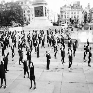 """Group stretch by Siliana: In 2016 MyLondon exhibition. """"It was the first day I collected the camera. I saw people starting to gather around in Trafalgar Square. The security guard said it was going to happen 'any minute now' but in the end I waited four hours just for the dance. A friend of mine was with me, she told me it's something that happens every year. A dance where people enjoy, where people of all ages dance all together. This was their warm up when they were stretching."""" Siliana squats in a church in south London, but it's """"under threat"""" and she's unsure of the future. She says the squat had 30 to 40 people living in it but when they had the court papers given to them many people left. Siliana was in the calendar last year and is now active in the Café Art photography mentoring group run by volunteers from The Royal Photographic Society which meets up every two weeks to learn photography skills with digital cameras."""