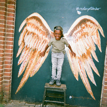 "COVER OF 2018 CALENDAR: Angel Kid, Shoreditch: This shot was taken in Shoreditch, one of Maya's favourite parts of the city, ""I'm always there. My model is Jonathan, the son of two of my best friends. He's five years old. It's such a sweet age: full of curiosity and still so innocent."" ""You hear that old adage never work with kids, but because he's my little buddy, making him smile and laugh for the photo wasn't an issue. I had a vision for capturing this spot, but when we arrived I realised he wasn't tall enough to fit the wings, so had to find something to add a bit of height. I asked around eventually managed to borrow this mini step ladder which was perfect."" Maya is a born and bred Londoner who loves her home city and enjoys photographing it. She has previously taken part in this contest three times, with her photos being selected for the calendar four times: 3 in 2013 and 1 in 2015."