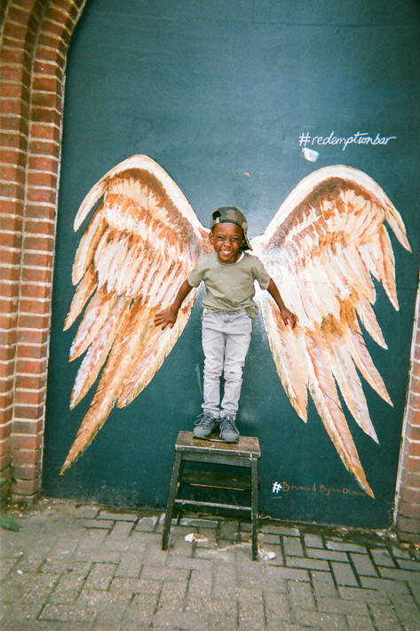 """COVER OF 2018 CALENDAR: Angel Kid, Shoreditch: This shot was taken in Shoreditch, one of Maya's favourite parts of the city, """"I'm always there. My model is Jonathan, the son of two of my best friends. He's five years old. It's such a sweet age: full of curiosity and still so innocent."""" """"You hear that old adage never work with kids, but because he's my little buddy, making him smile and laugh for the photo wasn't an issue. I had a vision for capturing this spot, but when we arrived I realised he wasn't tall enough to fit the wings, so had to find something to add a bit of height. I asked around eventually managed to borrow this mini step ladder which was perfect."""" Maya is a born and bred Londoner who loves her home city and enjoys photographing it. She has previously taken part in this co"""
