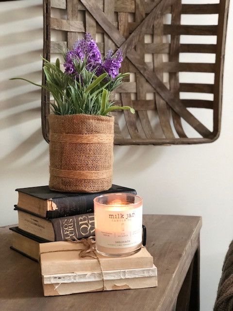 wood table with stacked books and candle, purple flowers in burlap, tobacco basket