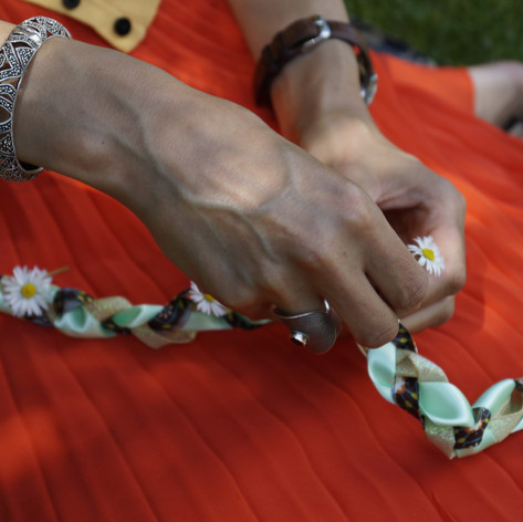Threading daisies through a handfasting cord.