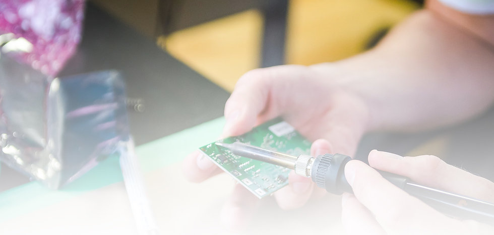 Closeup photo of Nymi employee soddering a piece of an electric circuitboard.