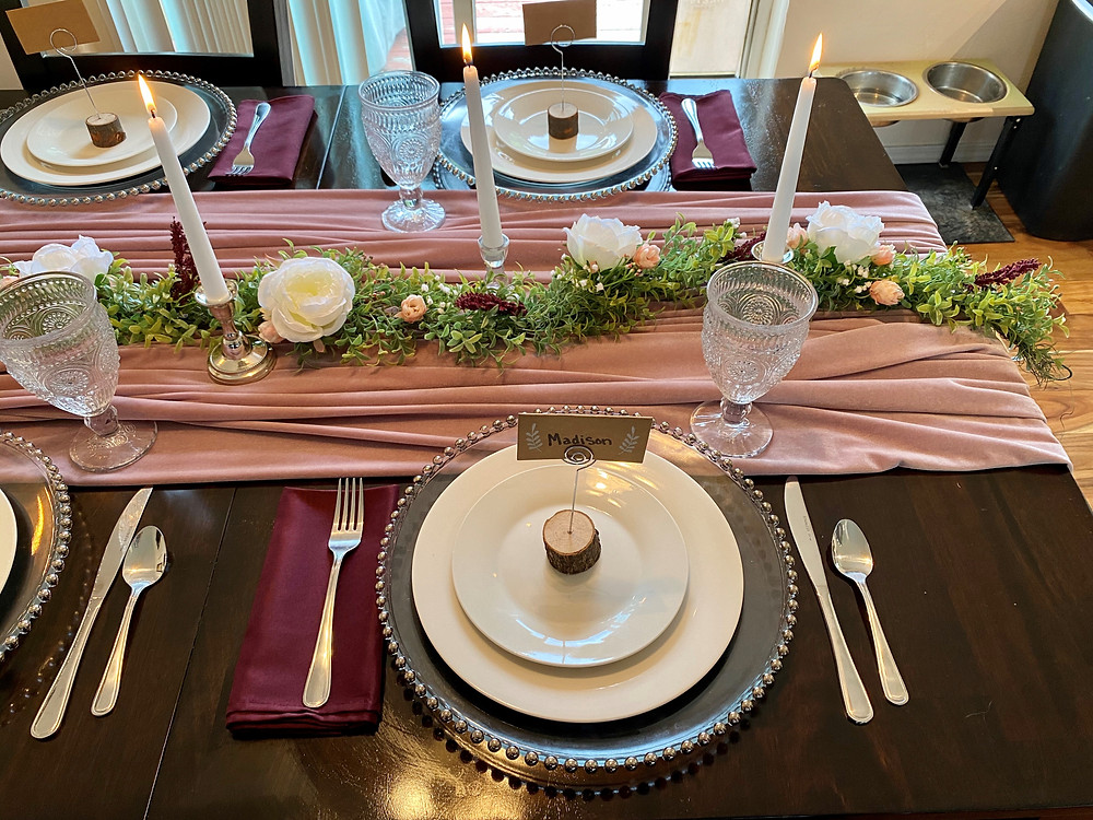 Table setting with silver beaded glass chargers, white china, silver silverware, burgundy napkins, crystal glassware and log round placecard holders