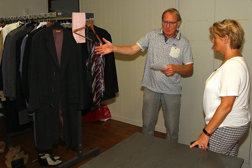 Burgemeester Sijbers bekijkt de kledingstukken die in het stuk gedragen worden.