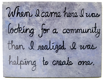 "A handwritten notice saying:""When I came here I was looking for a Community, then I realized I was helping to create one"""