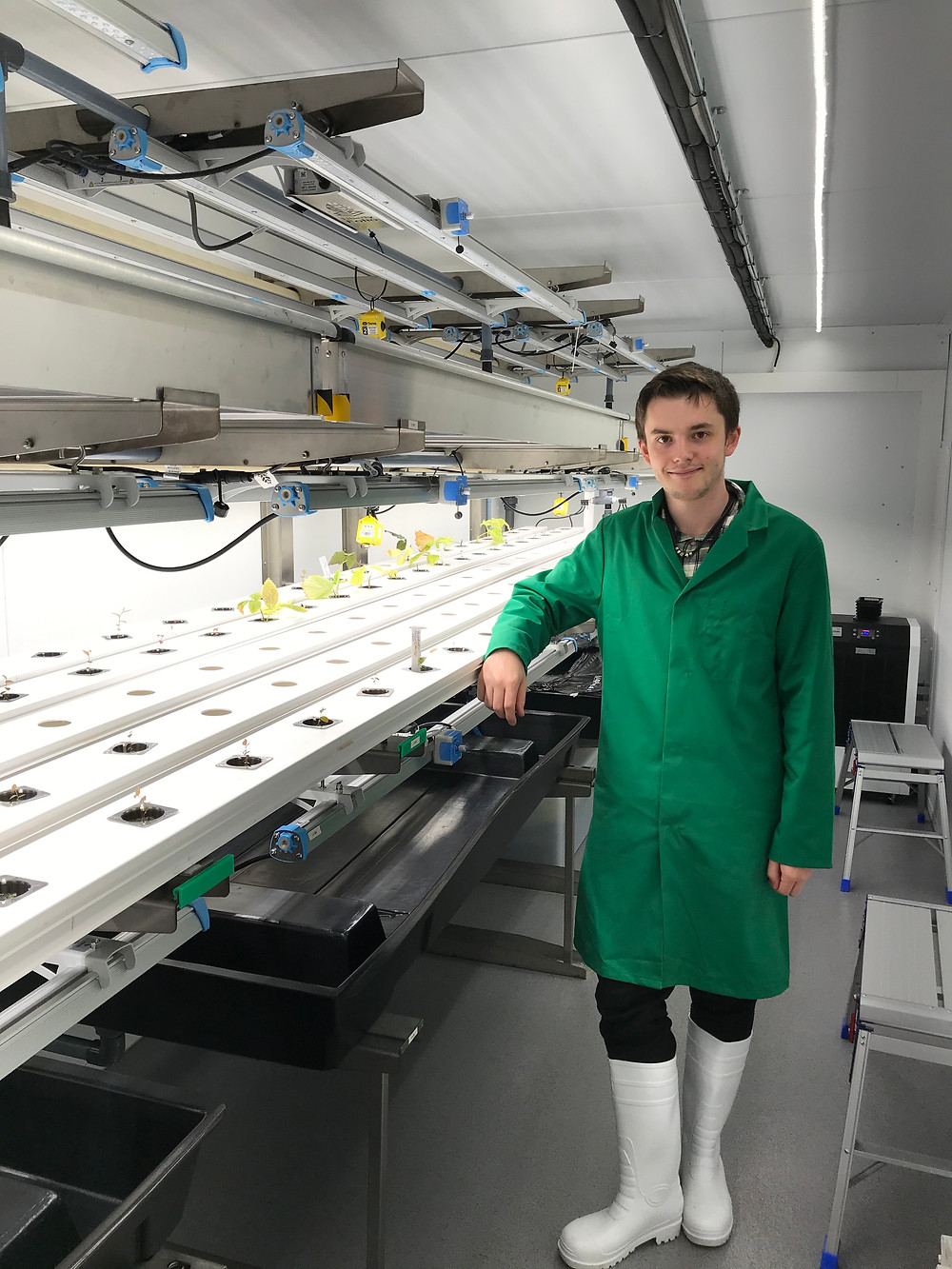 Scientific research assistant standing in front of vertical farming (controlled environment) equipment