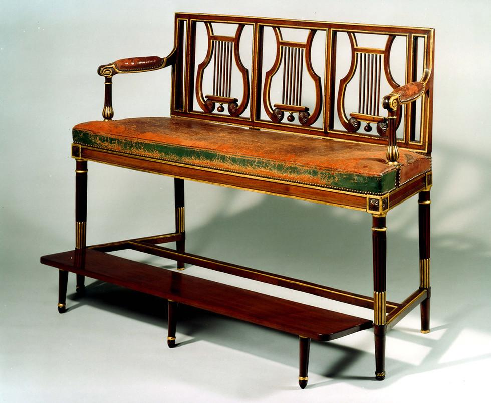 Banquette de billard d'époque Louis XVI, en acajou, le dossier à lyres, les pieds cannelés, l'assise recouverte de maroquin, le repose pieds est mobile. Estampillée Georges Jacob, maître en 1765. Vers 1785 H: 100, L: 147 cm, P: 42 cm.