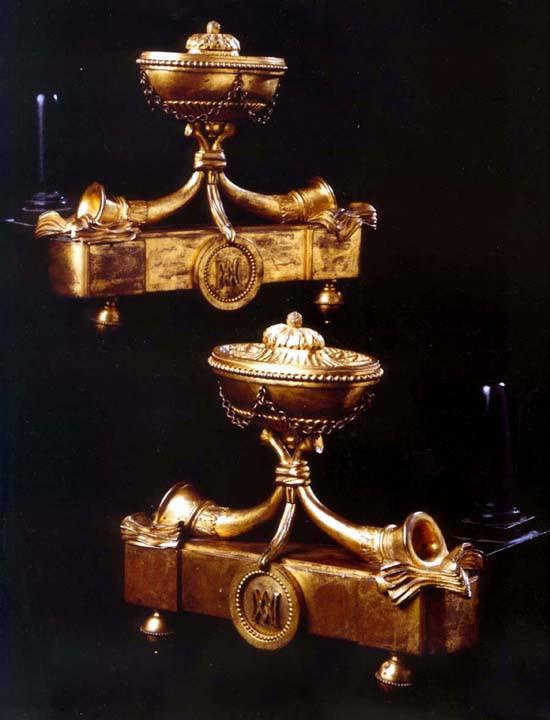 Paire de Chenets d'époque Louis XVI en bronze doré, en forme de trompes soutenant une cassolette, et reposant sur des feuillets de partition. Vers 1780 H: 18 cm, L: 24 cm