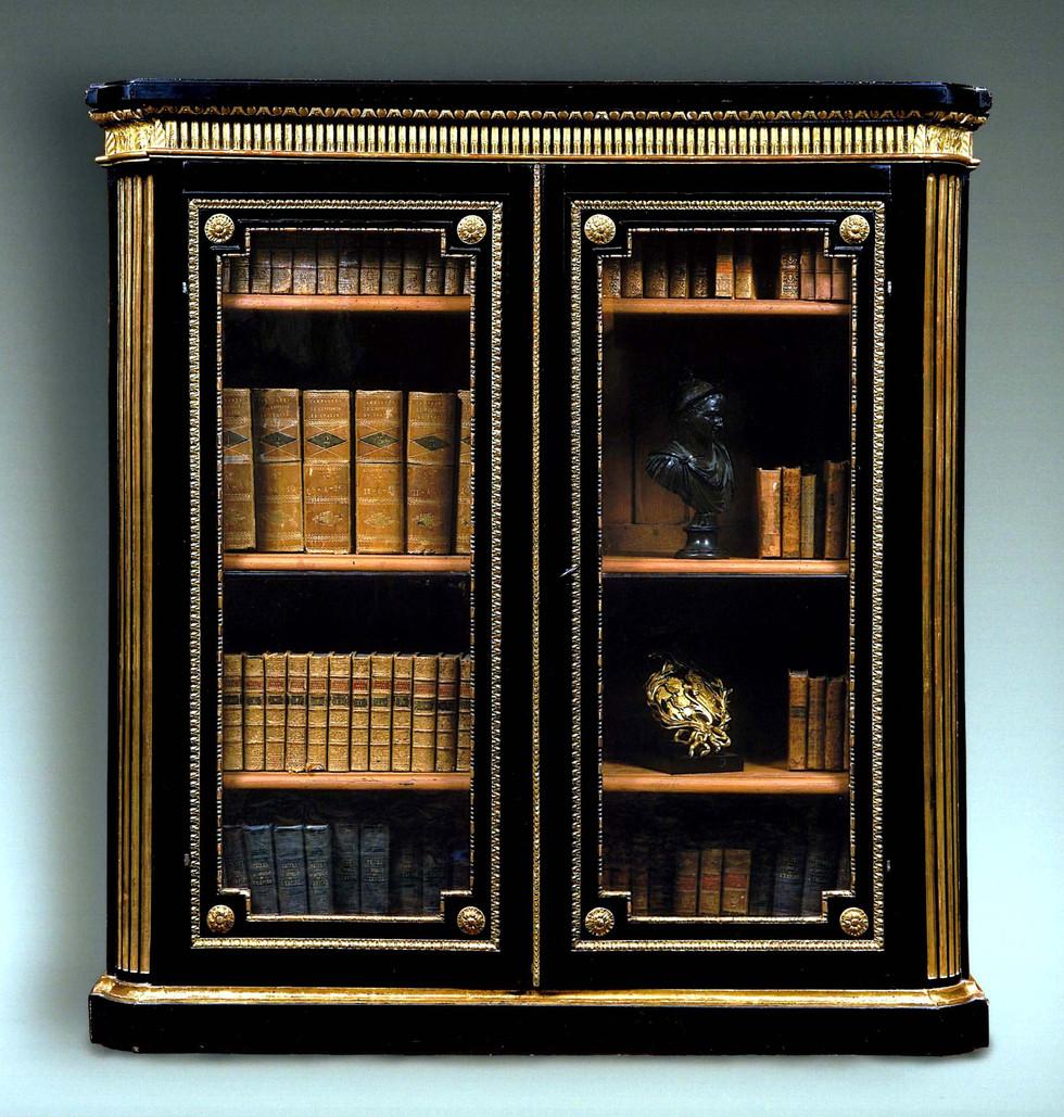 Bibliothèque vitrée démontable d'époque Louis XVI. Bois sculpté, noirci et doré. Paris, vers 1775. H 139 cm, L: 129 cm, P: 41 cm