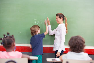 Teacher congratulating with kid in prima