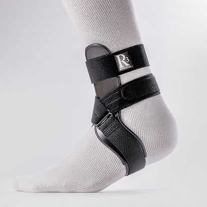 Sleek design of the R3 Sport Ankle Brace is pictured here. Features a mechanical strut that wraps from lower shin down and over to the outside bottom of the foot, top strap secures around the upper ankle, and lower strap creates a figure-8 around the low ankle and under the foot