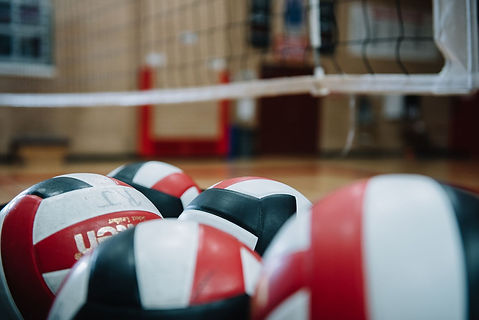 Red, black and white volleyballs fill the bottom of the the image and the net and court in the background are out of focus