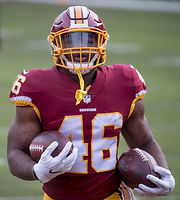 Professional athlete LeShun Daniels Jr is pictured wearing his Washington Redskins NFL uniform in 2017, holding 2 footballs and lookng through the mask on his football helmet