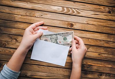 Person holding a ten dollar bi