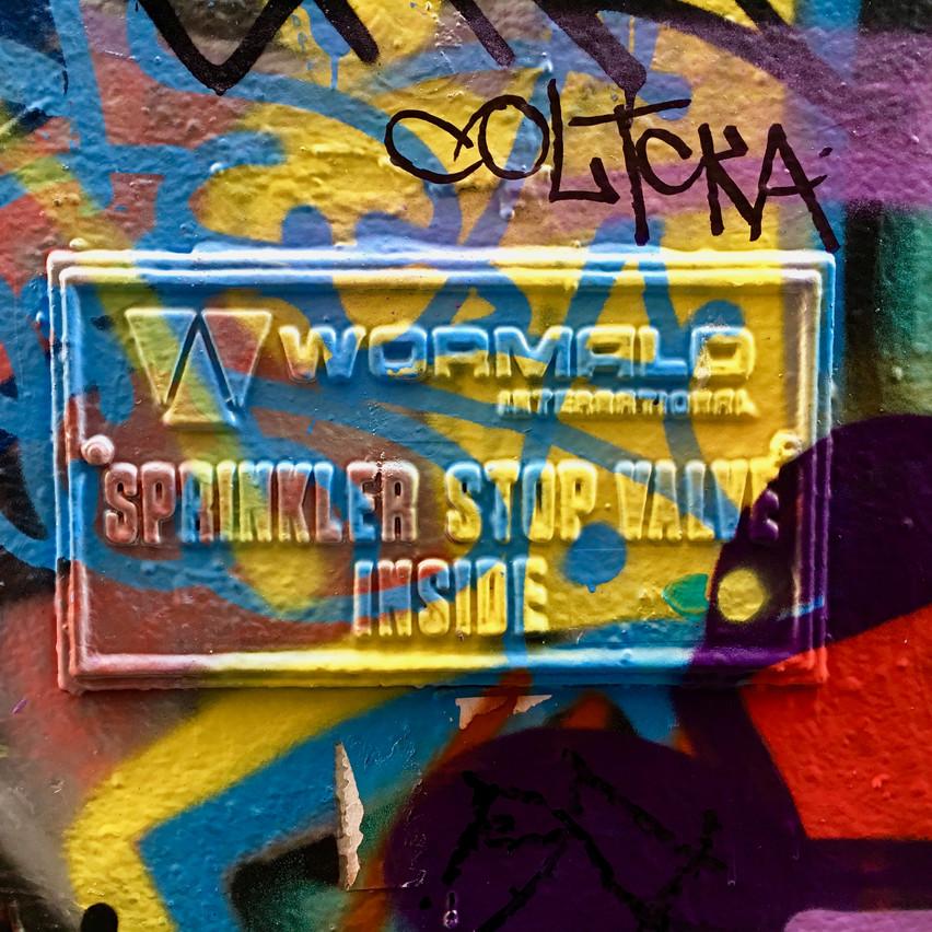 Graffiti splattered paint over Sprinkler Stop Valve sign | Union Lane