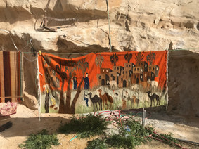 Handmade wall hanging of desert scene with houses and camels