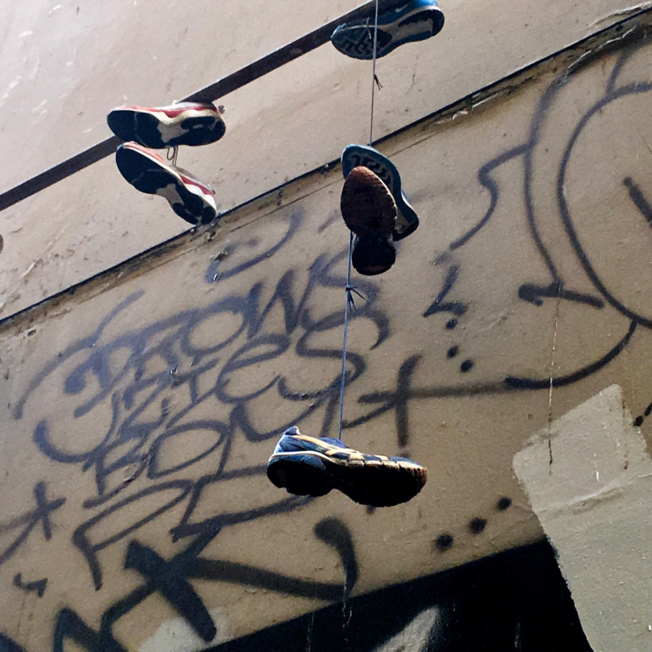 Sneakers dangling from iron pipe | Union Lane