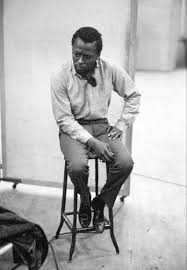 Kind of Blue recording sessions: Miles Davis sitting on stool in recording studio