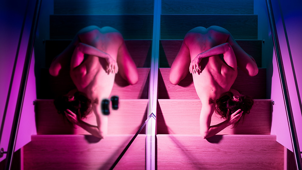 Red purple and blue lit fine art female nude posed on steps NSFW