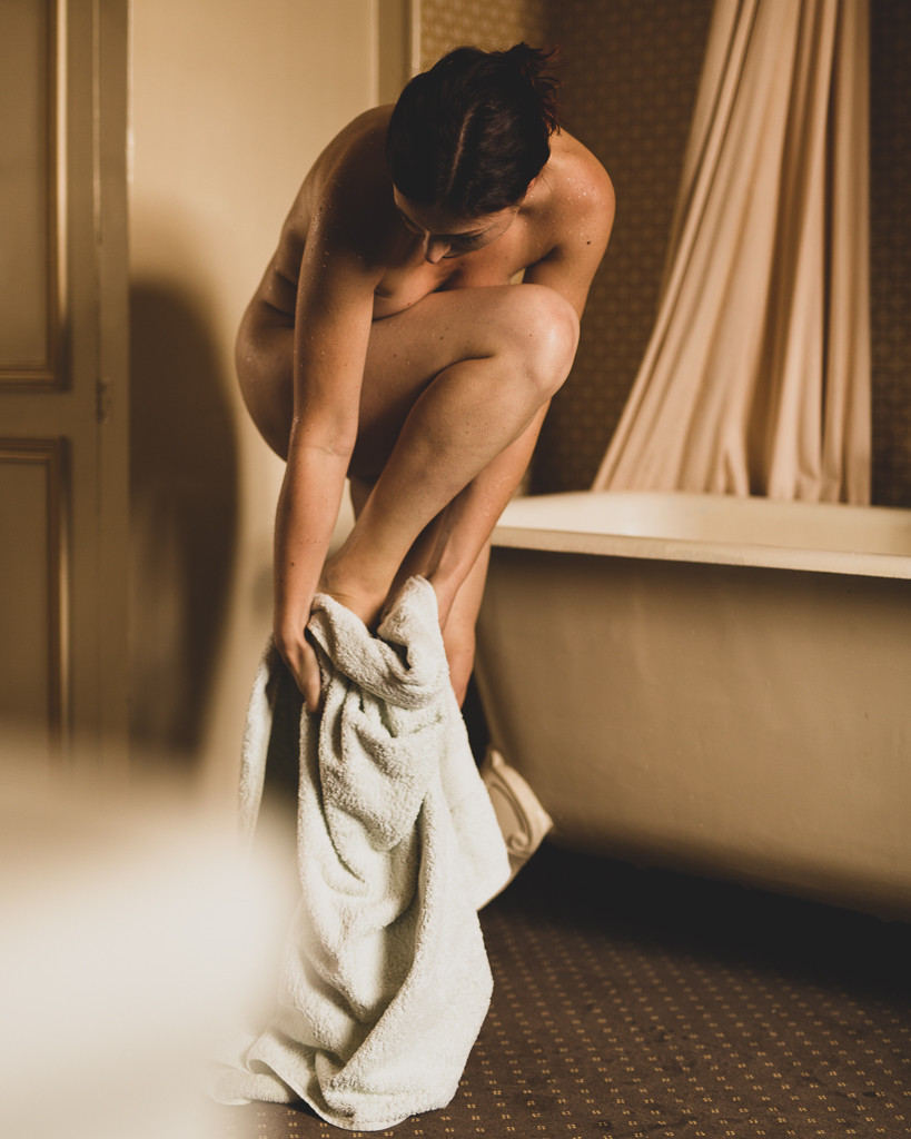 Woman drying herself with white towel by clawfoot bath in evening light