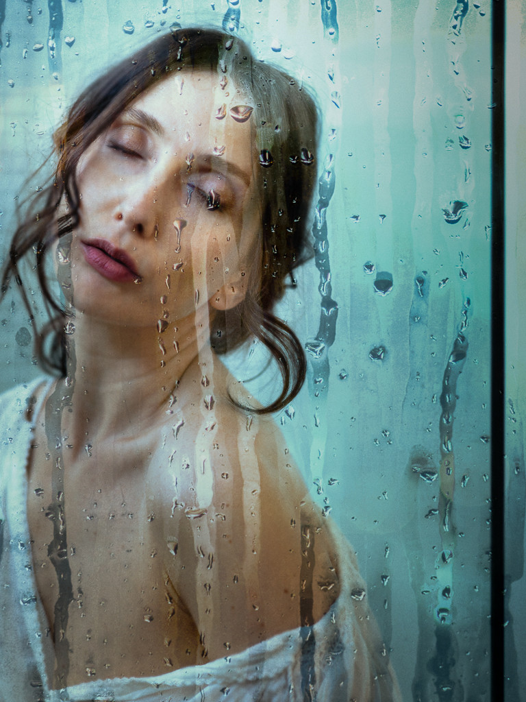 Beautiful woman with eyes closed wearing white top off shoulder behind wet glass