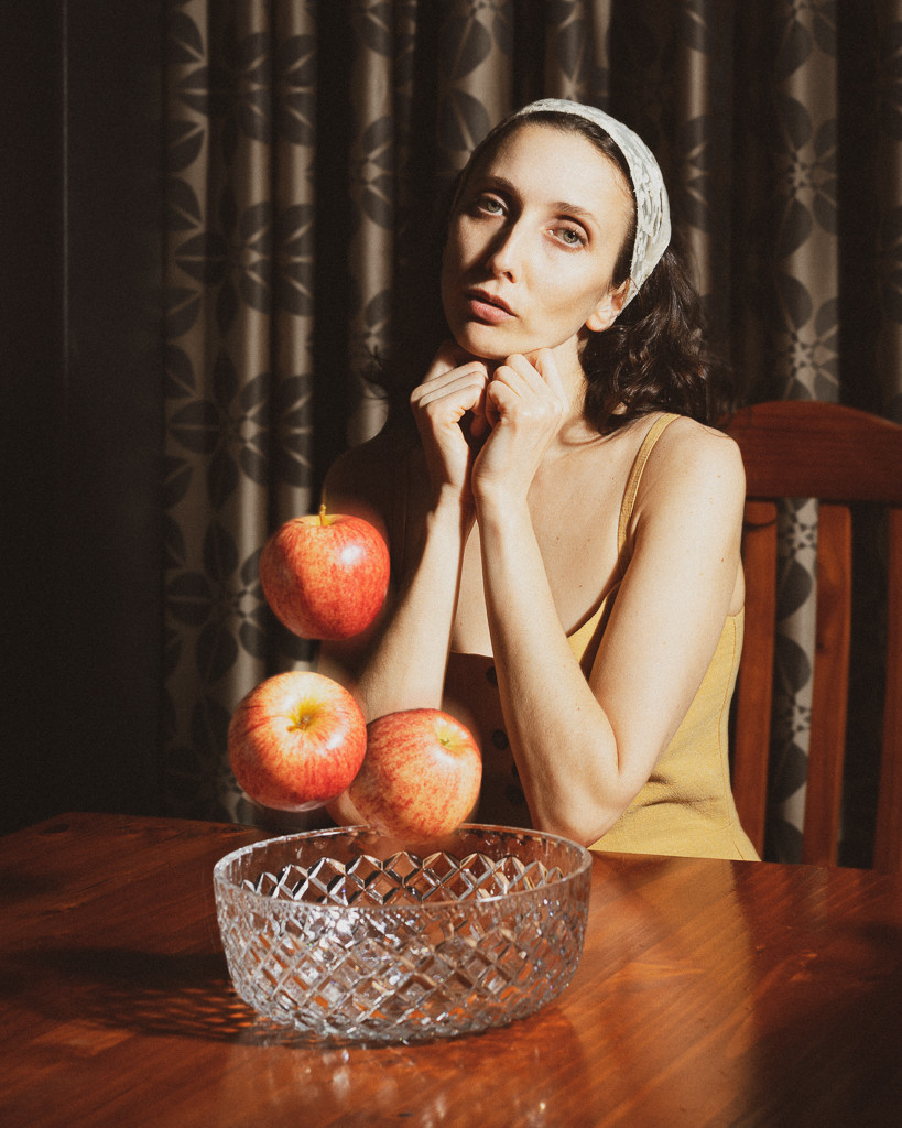 Clothed woman wearing headscarf seated at wood table with apples levitating from cut glass bowl