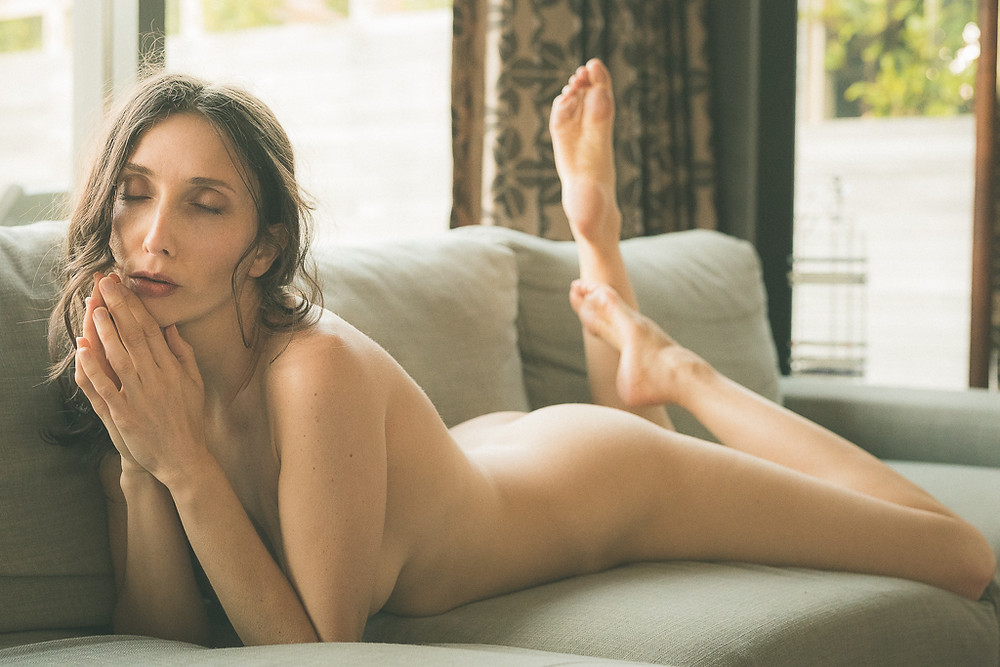 Implied nude beautiful woman reclining on sofa in natural light in NSFW art