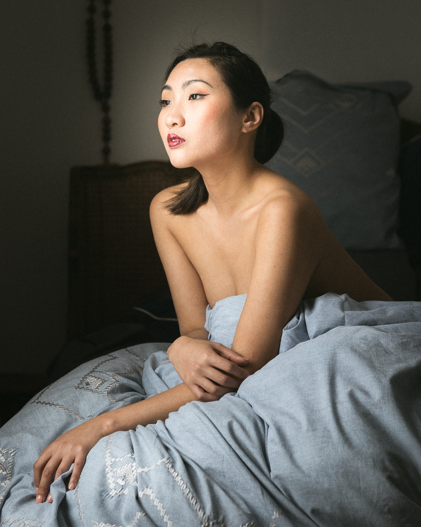 Beautiful young Asian woman seated under patterned blue duvetlooking dreamily to left