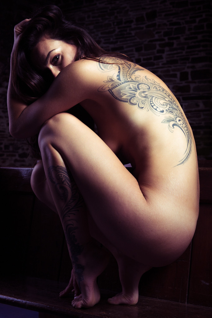 Implied art nude female tattooed model crouching on pew NSFW