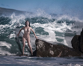 Naked woman about to be engulfed by a big wave on a rocky beach