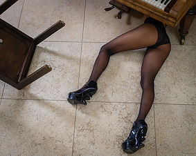 Woman in tights and black knickers wearing exotic high highs part hidden under piano NSFW